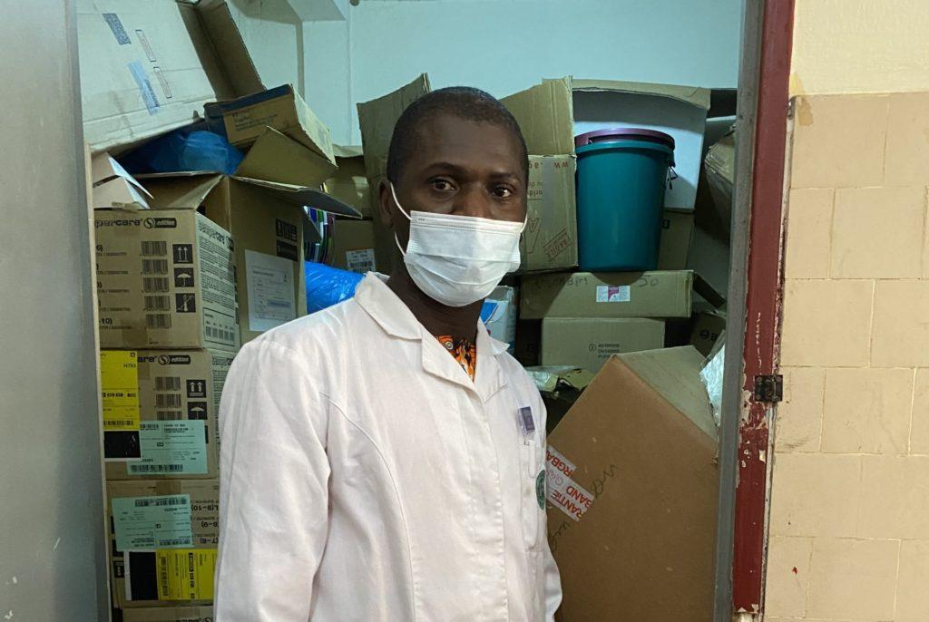 Dr Gabriel GOEPOGUI, Service pédiatrie-Hôpital Ignace Deen, point focal du projet Isanco devant le stock de matériel d'hygiène et de protection fournis dans le cadre du projet Isanco pour mieux protéger le personnel de santé et les patient·es qui fréquentent le service.